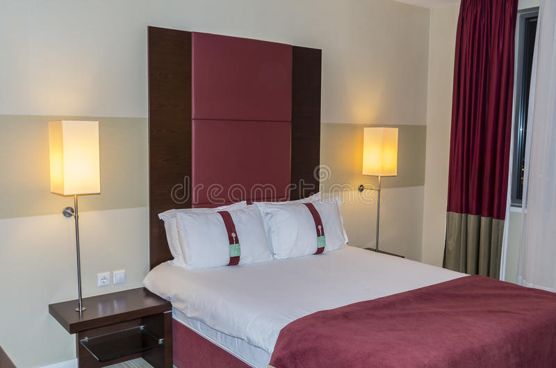 Hotel bedroom. With bed curtains and lights royalty free stock images