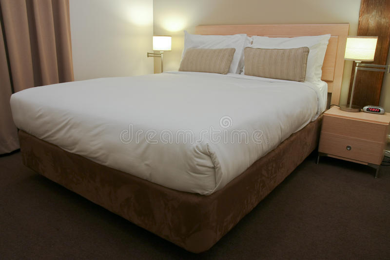 Hotel bedroom with bed and side lamps royalty free stock photography
