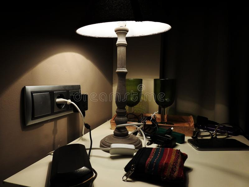 Hotel bedside table with loaders and various tools. Bedside table in a hotel with all kinds of gadgets ready to be used stock photo