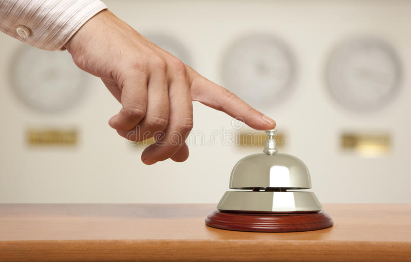 Hotel bell. Hand of a businessman using a hotel bell royalty free stock images