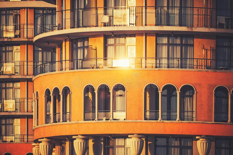 Hotel building architecture, exterior of windows and balconies and morning sun reflection royalty free stock images