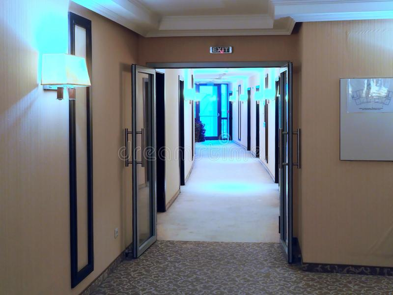 Hotel Corridor Leading to Glass Window. A long carpeted hotel corridor with wall mounted lights with warm neutral colours stock images
