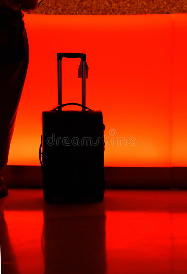 Hotel counter with luggage at night. A luggage with pulling handle extended in front of a orange-light illuminated hotel counter royalty free stock photos