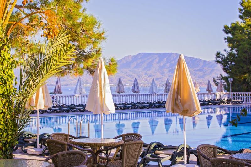 Hotel de gran altura cómodo Hotel vacío, piscina, mar, palmeras, paraguas, tablas, camas del sol, montañas en el fondo foto de archivo libre de regalías