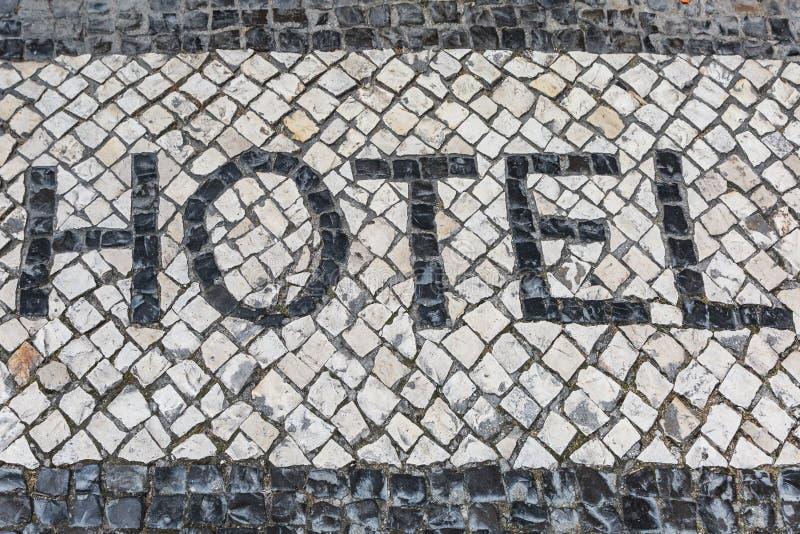 Hotel de la palabra en un piso de mosaico típico en la calle de Lisboa, Portugal fotos de archivo