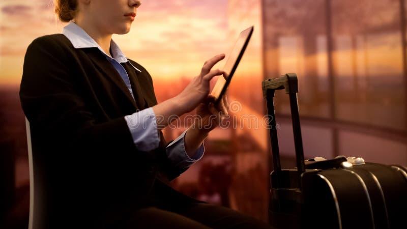 Hotel de la reservación de la mujer en la tableta mientras que espera el vuelo en el aeropuerto, viaje de negocios fotografía de archivo