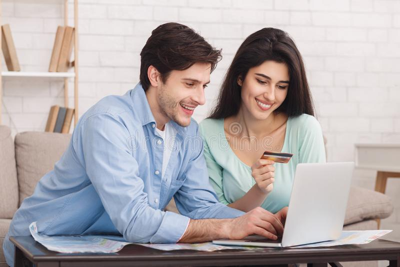 Hotel di prenotazione delle coppie felici online sul computer portatile immagine stock