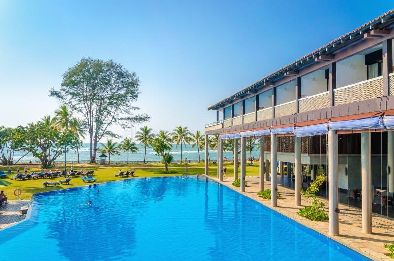 Hotel e piscina de Luxuary contra palmeiras fotos de stock royalty free