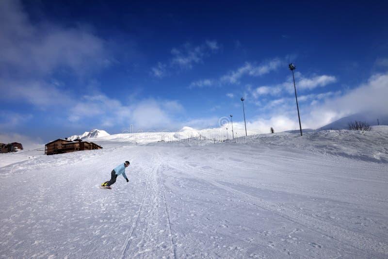 Hotel em montanhas e em snowboarder do inverno na inclinação fotos de stock