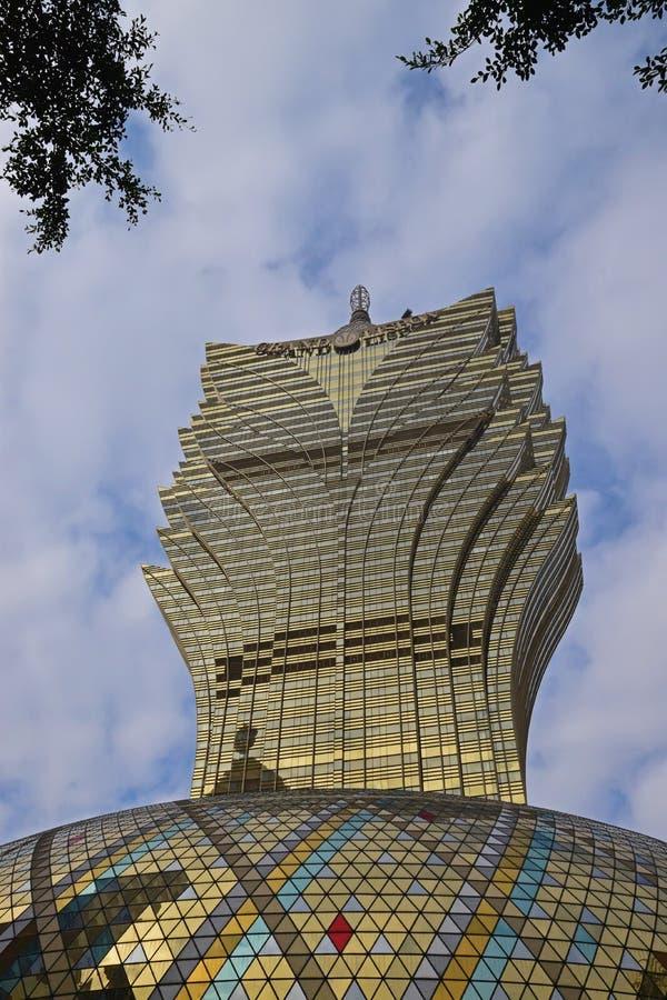 Hotel grande de Lisboa em Macau que assemelha-se ao teste padrão das folhas com as folhas reais das árvores que aparecem na parte imagem de stock royalty free