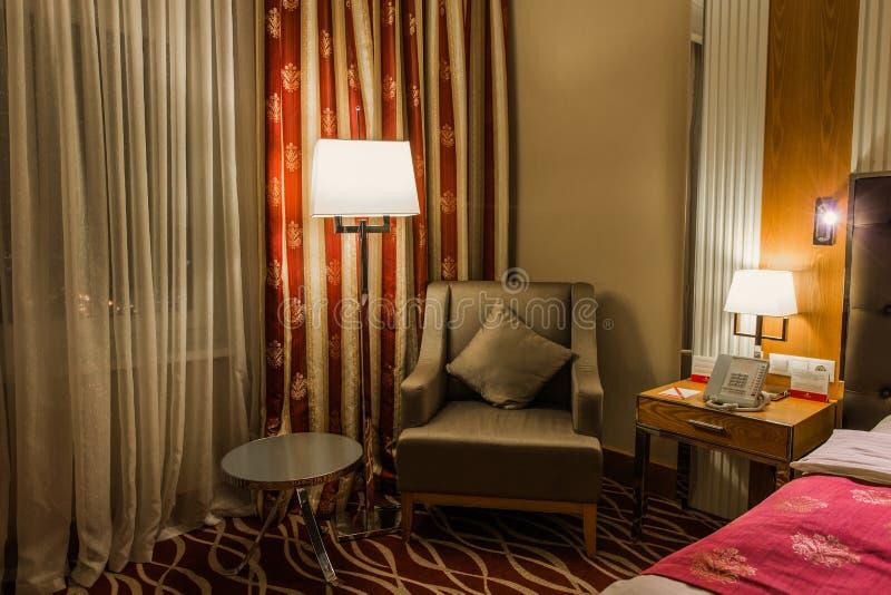 Hotel, kleiner Rundtischstuhl nahe bei einer Stehlampe auf einer kleinen Tabelle nahe dem Bett ist ein Telefon und eine Lampe stockbild