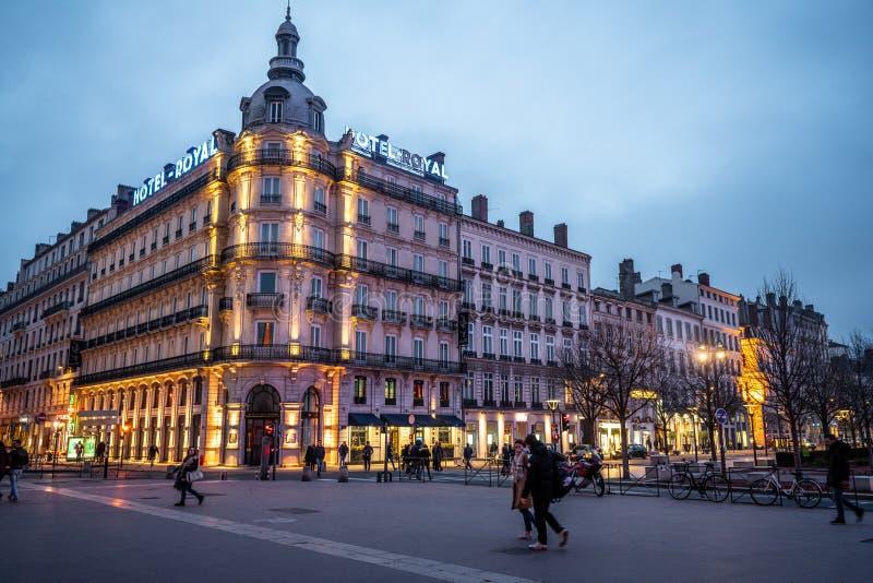 Hotel Le Royal-byggnaden ser ett lyxhotell på MGalery på natten och människor på Place Bellecour Square i Lyon France royaltyfri foto