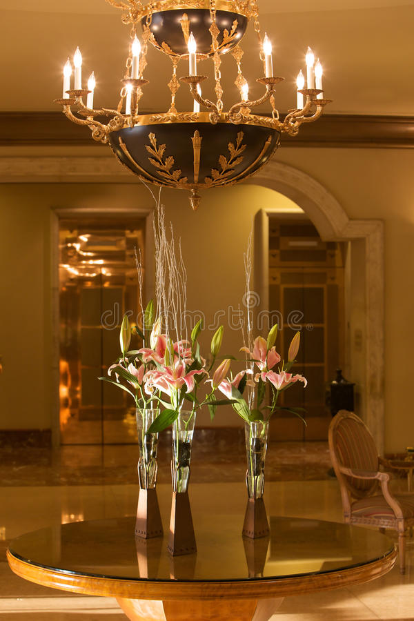 Hotel lobby with chandelier and flowers royalty free stock images