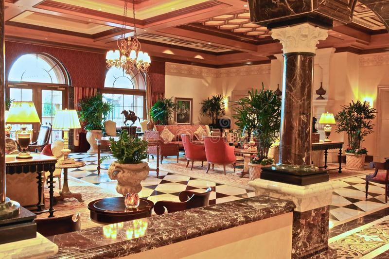 Hotel lobby luxury. Fancy hotel lobby with marble columns chandlers and fancy furniture royalty free stock images