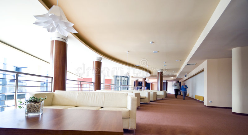 Hotel lobby sofas. A spacious interior of a modern hotel with leather sofas at the side. Two people walking in the distance (motion blurred stock photos
