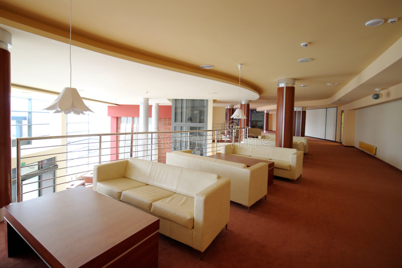 Hotel lobby sofas. A spacious interior of a modern hotel with leather sofas at the side stock image