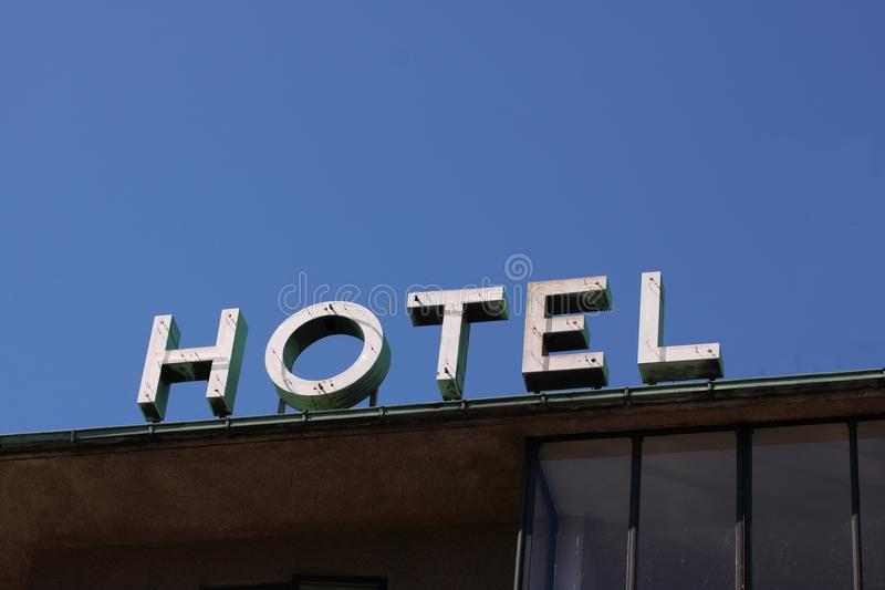 Hotel logo placed on a building against a clear blur sky with copy space for writing. Minimalistic modern stock photo. Anonymous hotel logo placed on a building royalty free stock photography