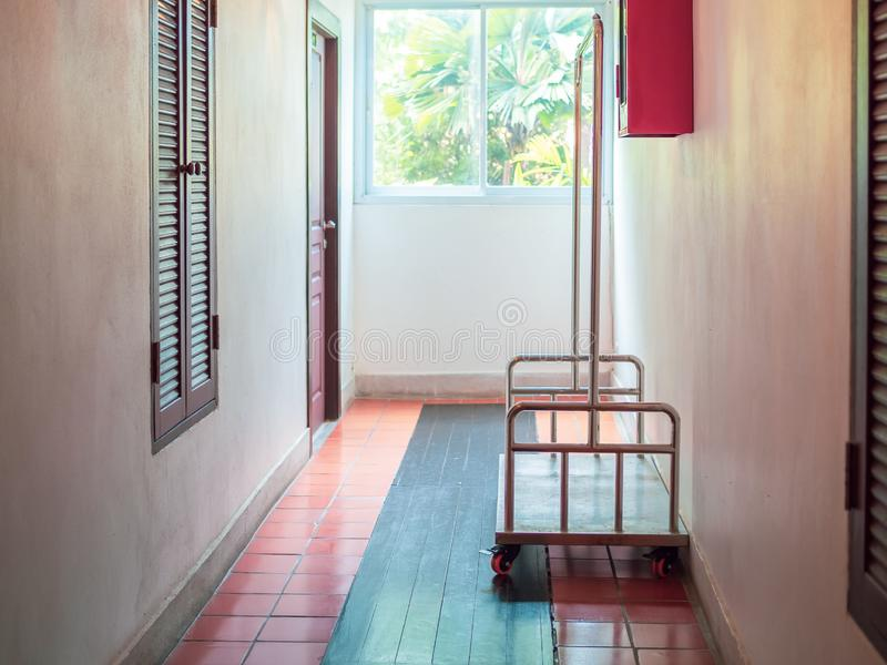 Hotel luggage cart in hotel. Empty hotel luggage cart on walkway in front of the door room in low cost hotel royalty free stock image