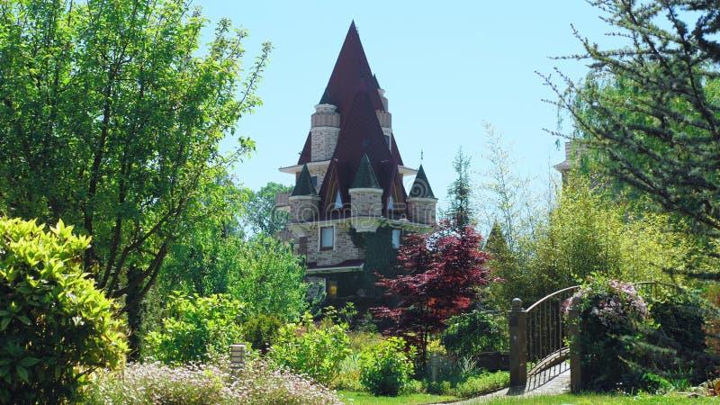 Hotel luxuoso no estilo vitoriano, imergido em ?rvores e em arbustos bonitos telhados com spiers em um fundo de claro imagens de stock