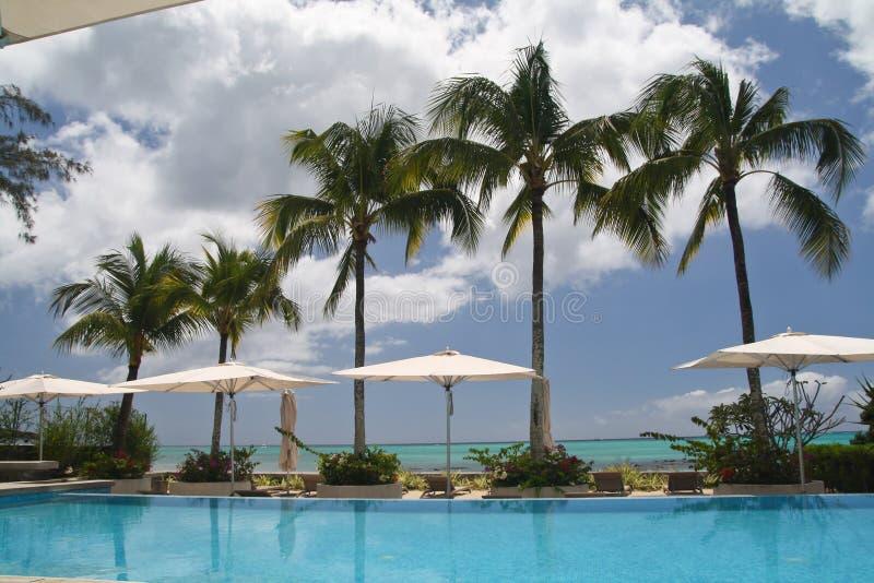 Hotel mit Swimmingpool und Palmen lizenzfreie stockfotografie