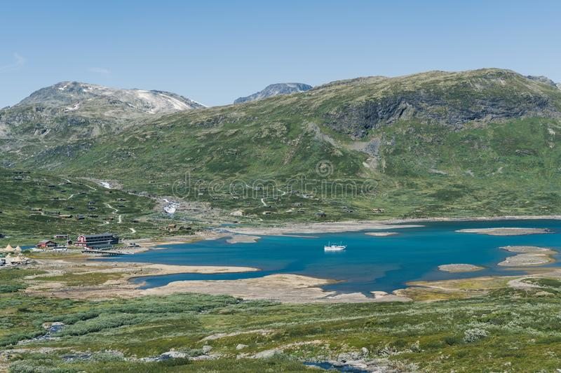 Hotel in the mountain valley village, with a pier for the small vessels in Norwegian highland. Region of Oppland royalty free stock photo