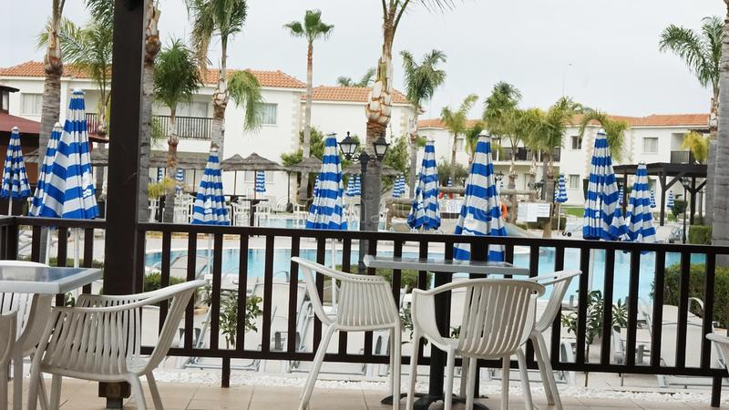 Hotel pool in Cyprus in spring. Water umbrella blue terrace table chairs palm trees stock images