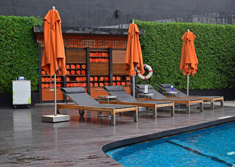 Hotel pool side setup with large umbrella, cushion sundeck chair & rolled towels in cabinet. Hotel pool side orange themed setup with large umbrella, cushion stock photography
