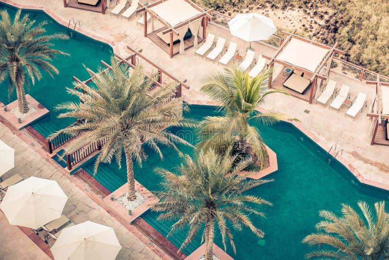Hotel Poolside mit Sonnenschirmen und Palmen lizenzfreie stockbilder
