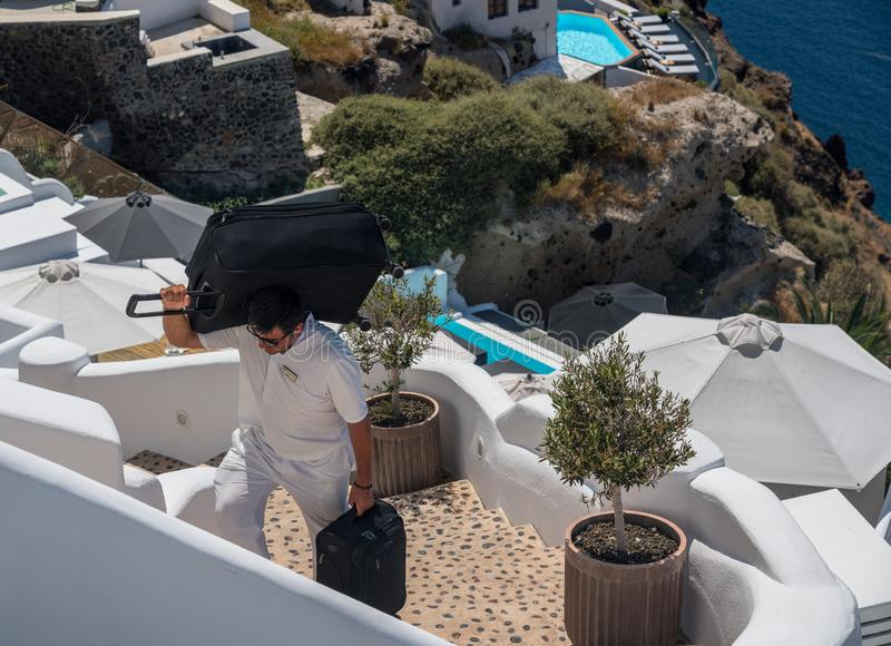 Hotel porter carries luggage up cliff in Oia. SANTORINI, GREECE - 18 MAY 2019: Hotel porter carries luggage up cliff steps in village of Oia on Santorini stock images