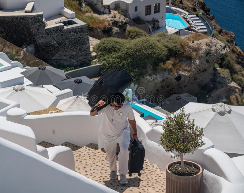 Hotel porter carries luggage up cliff in Oia. SANTORINI, GREECE - 18 MAY 2019: Hotel porter carries luggage up cliff steps in village of Oia on Santorini royalty free stock photo
