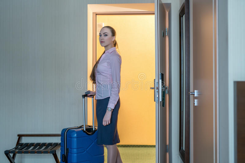 Hotel. Pretty woman with luggage entered into room. Hotel. Beautiful woman with luggage entered into room stock photography