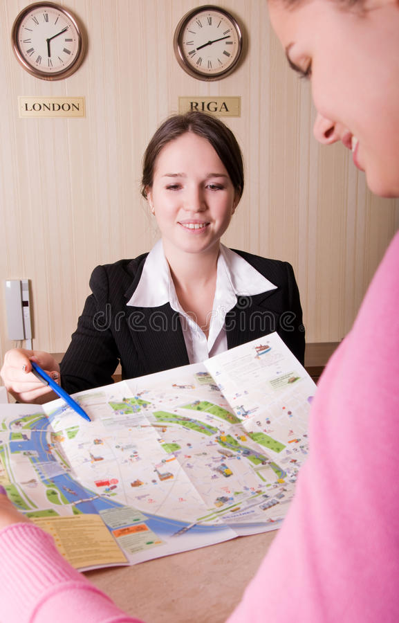 Hotel reception. Receptionist showing the way on the map stock photography