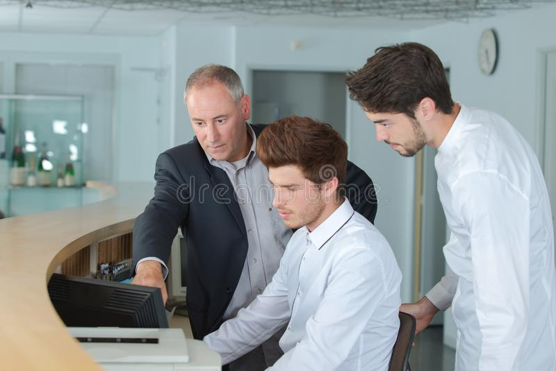 Hotel receptionist apprentices with teacher. Receptionist stock photos