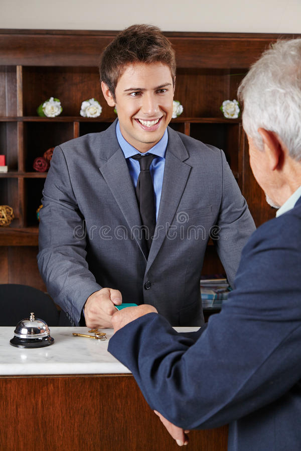 Hotel receptionist giving key card to senior. Happy hotel receptionist giving key card to senior man royalty free stock photography