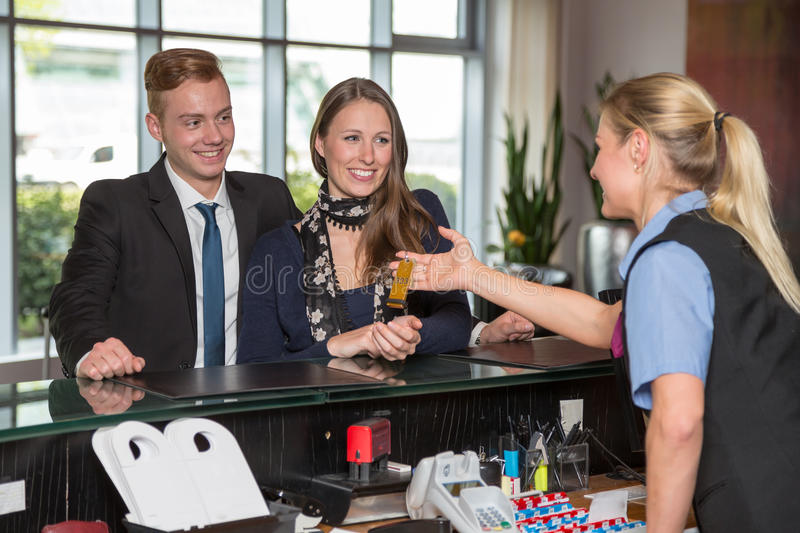 Hotel receptionist handing over key to customers. Hotel receptionist handing over key to two customers royalty free stock photo