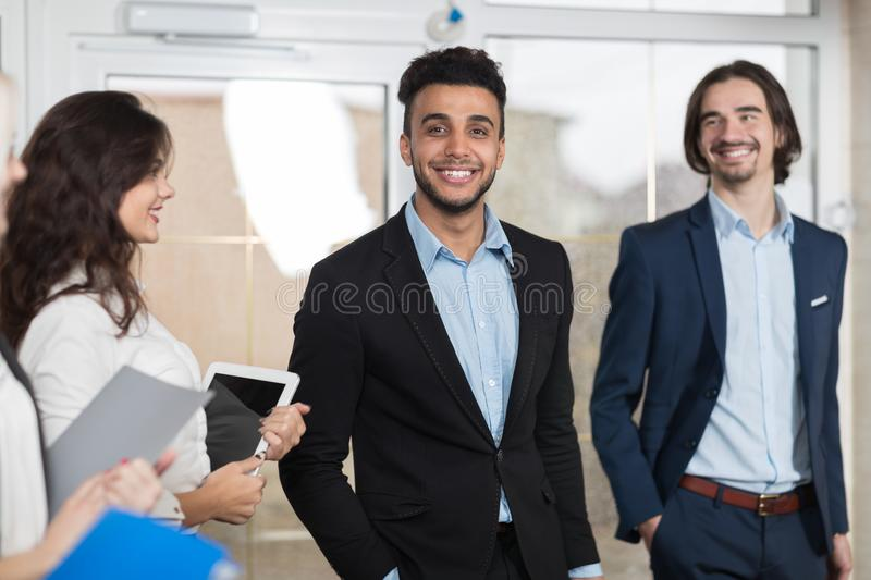 Hotel Receptionist Meeting Business People Group In Lobby. Guests Arrive stock photography