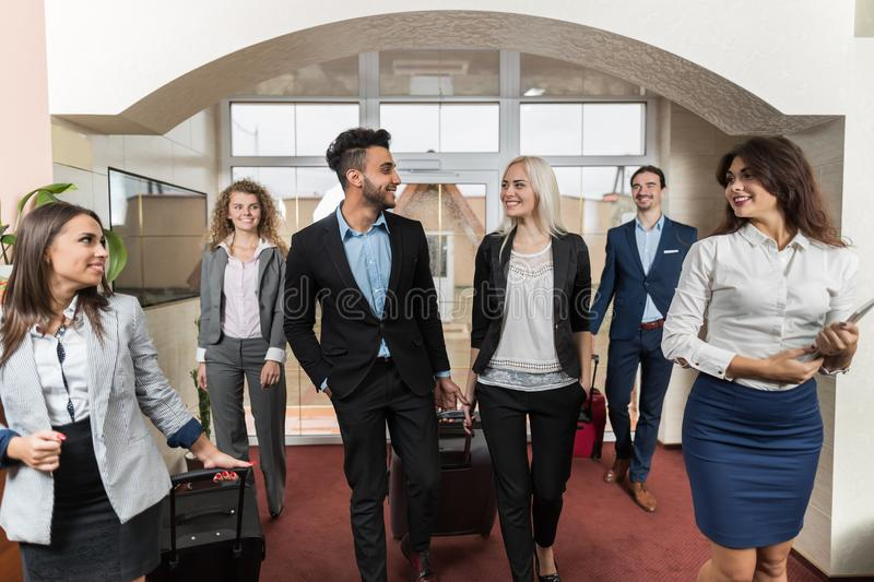 Hotel Receptionist Meeting Business People Group In Lobby. Guests Arrive stock image