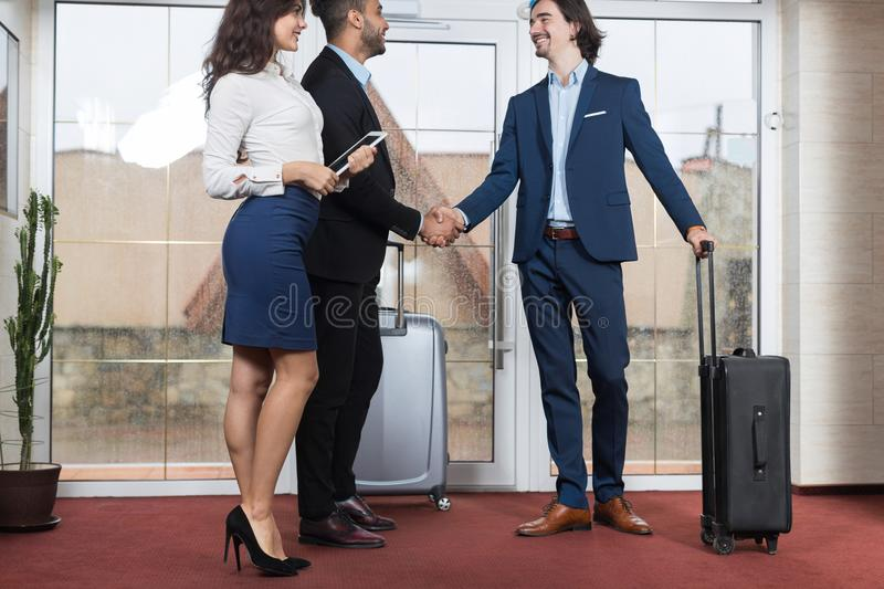Hotel Receptionist Meeting Business People Group In Lobby, Two Businessman Meeting Handshake. Guests Arrive stock photography