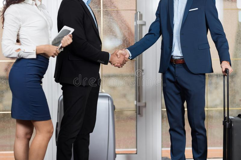 Hotel Receptionist Meeting Business People Group In Lobby, Two Businessman Meeting Handshake. Guests Arrive royalty free stock image