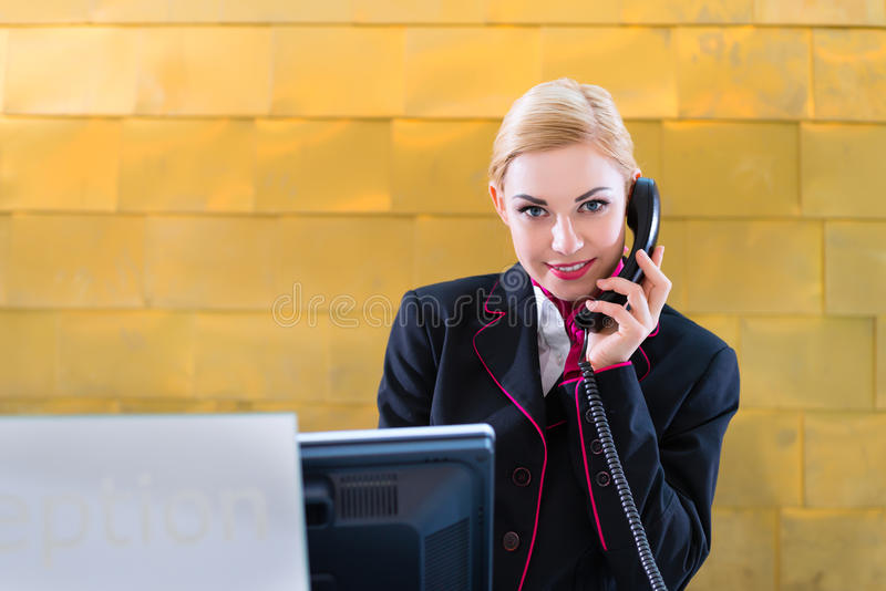 Hotel receptionist with phone on front desk. Is smiling royalty free stock photo