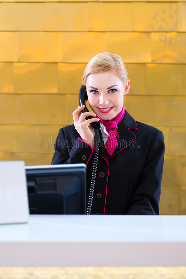 Hotel receptionist with phone on front desk stock images