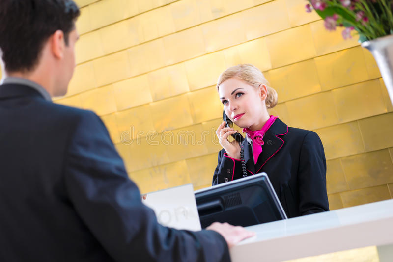 Hotel receptionist with phone and guest royalty free stock photography