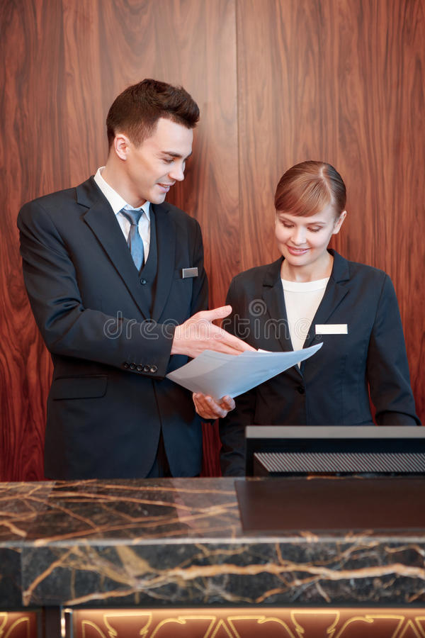 Hotel receptionists behind the counter stock photos
