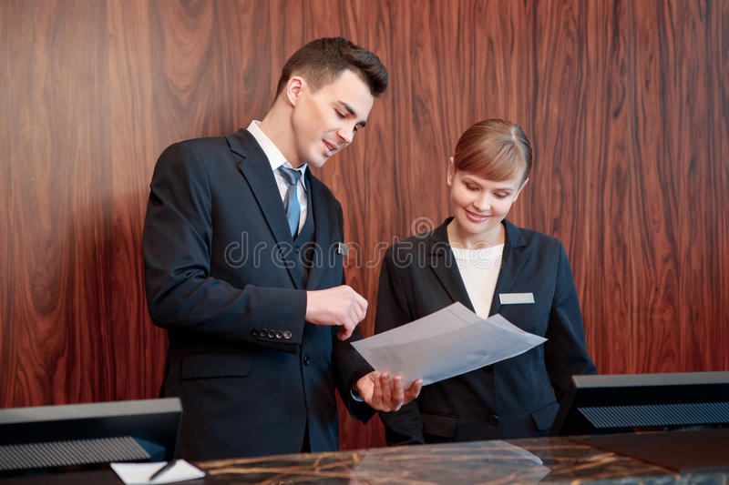 Hotel receptionists behind the counter stock photography
