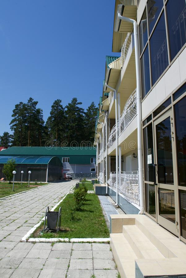 Hotel, recreation center, three-story building. With a large number of rooms for guests. Siberia, Altai Mountains, Russia stock image