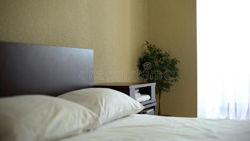 Hotel room with bed, cheap accommodation, economy class vacation, business trip stock photography