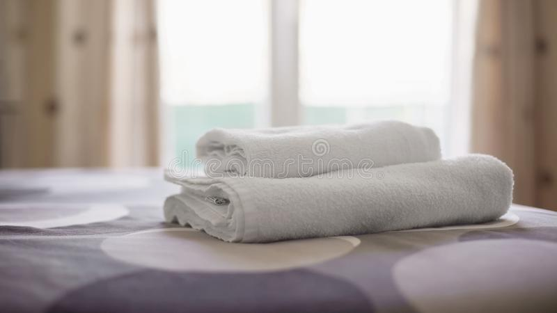Hotel room with clean towels on fresh bed linen, accommodation service quality. Stock photo royalty free stock photos