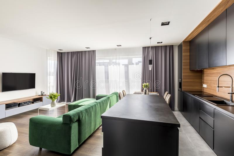 Hotel room interior with green lounge, TV set, windows with drapes and open space kitchen corner stock photos