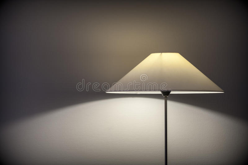 Hotel room lamp shade projecting light and shadows on the wall royalty free stock photo