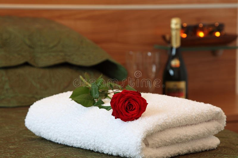 Hotel room with rose on bed.